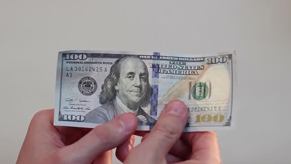Thumbnail for Person Holding in Hands and Turning Over One Hundred-Dollar Bill