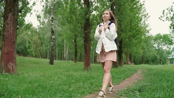 Beautiful Woman Smiles Walking Along Path Surrounded By Foliage and Trees