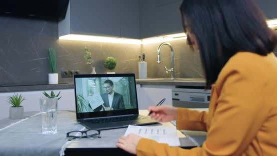 Woman Sitting in  Kitchen and Listening Explaining from Partner Via Video conference
