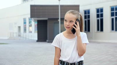 Blonde Girl with Long Hair in Ponytail Talks on Smartphone