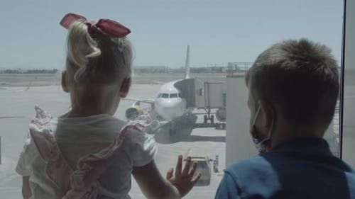 Siblings are interested in planes behind the glass. Waiting at the airport
