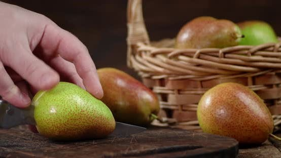 Thumbnail for Male Hand with a Knife Cut the Pear Into Two Halves.