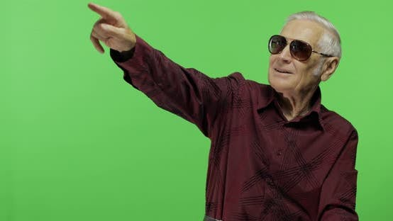 Thumbnail for Senior Man Tourist in Sunglasses Points at Something. Handsome Old Man