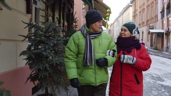 Senior Couple Grandmother Grandfather Tourists in Winter Jackets Clothing Walking Talking in City