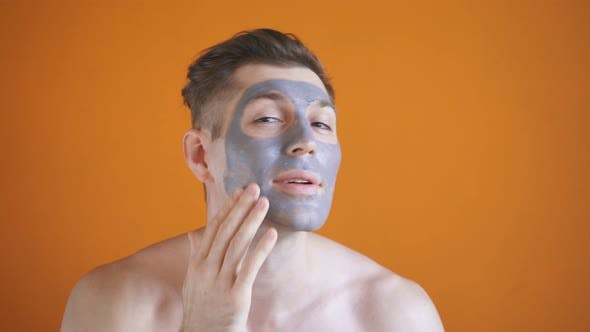 Young Man Applies a Gray Clay Mask To His Face, for Healthy Glowing Skin, Isolated Background