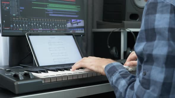 Thumbnail for Hands playing on electric midi keyboard piano at home music recording studio. Music concept