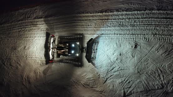 Thumbnail for Aerial View. Snow Grooming Snowcat Machines Fix Trail on Ski Resort Slope at Night.