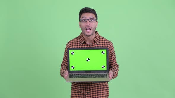 Thumbnail for Happy Young Hispanic Hipster Man Showing Laptop and Looking Surprised