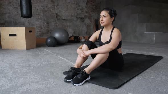 Sporty Indian woman sitting alone, leaving dark gym room feeling overwhelmed
