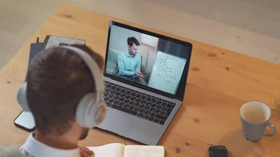 Man Student Sits at a Desk at Home and Study Online Using a Laptop Student Learns in a Remote Lesson