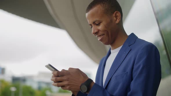 Thumbnail for Cheerful Handsome Young Man Using Smartphone