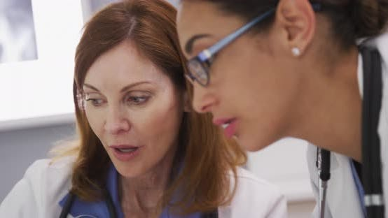 Thumbnail for Close up of latina doctor discussing with elder medical colleague inside office