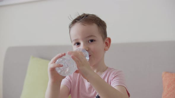 Cute Boy Drinks Water From a Bottle Sitting on the Couch at Home