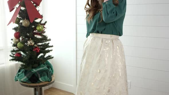 Thumbnail for Woman showing off dress standing next to christmas tree