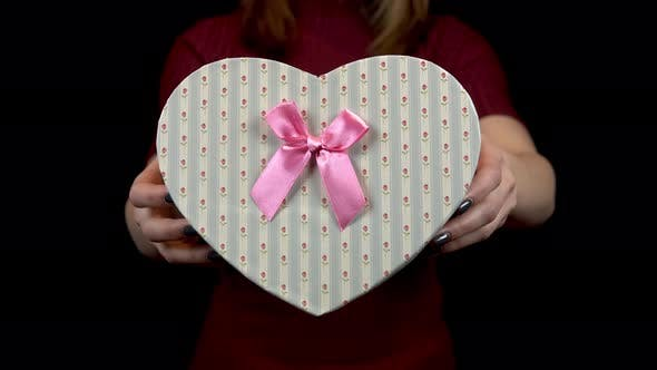 Thumbnail for A Young Woman Holds Out a Heart-shaped Box To the Camera. Woman Holding a Gift in Her Hands on a