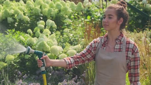 Young Female Gardener Watering Plants With Hose