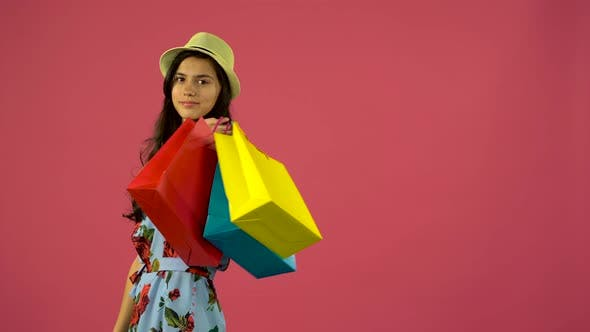 Thumbnail for Girl Posing on Camera with Multicolored Shopping Bags, Pink Background