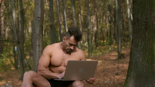 Thumbnail for Strong Naked Torso Guy Sits In An Autumn Park With Laptop In His Hands
