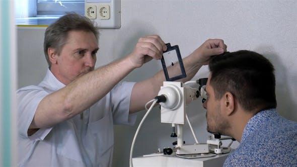 Thumbnail for Senior optometrist doing sight testing for patient