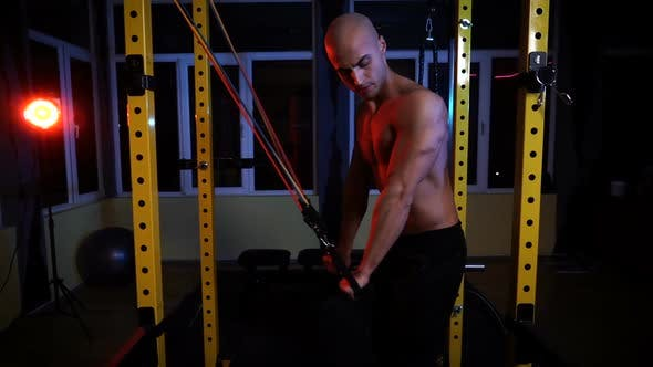 Male Bodybuilder Training with Resistance Bands for Triceps in the Gym