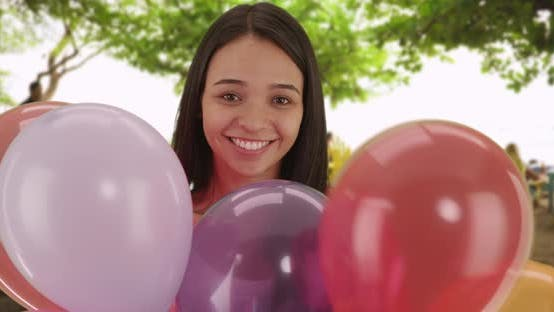 Thumbnail for Happy Hispanic woman holding balloons at the beach