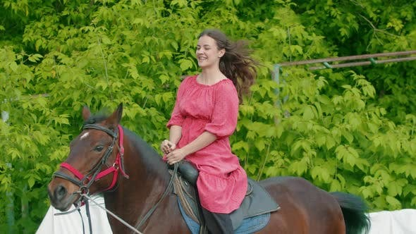 Thumbnail for Young Woman with Braces in Pink Dress Riding a Horse