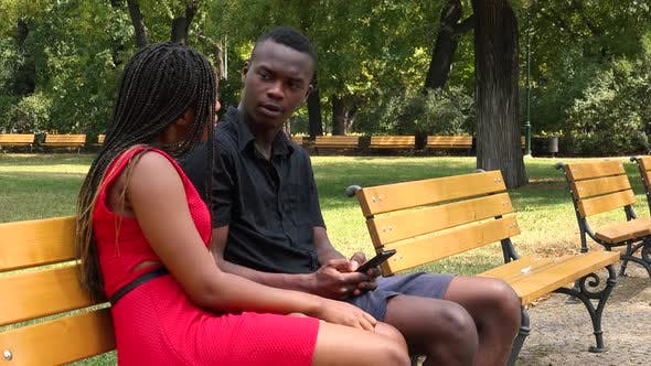 Thumbnail for A Young Black Couple Sits on a Bench in a Park and Works on a Smartphone