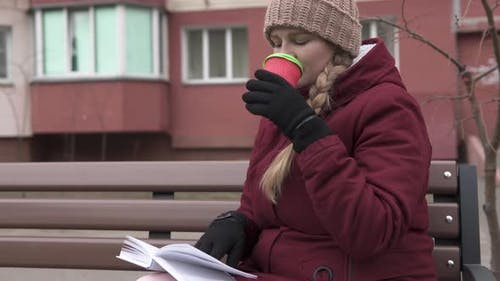 A Young Mother Reads a Book in the Fresh Air and Sips Aromatic Tea