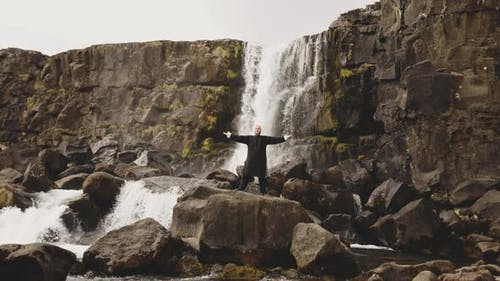 Kung Fu Master Performing Poses On Rocks By Waterfall