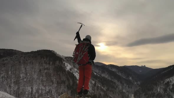 Thumbnail for The Silhouette of a Young Male Climber Standing on Top of a Mountain and Holding Up an Ice Axe