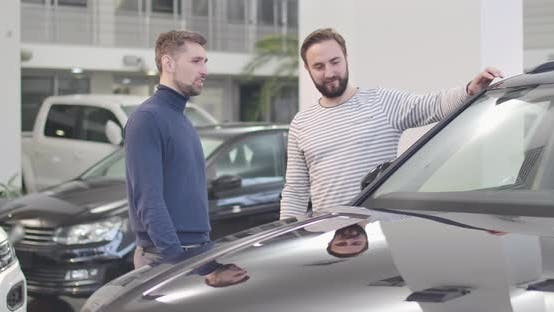 Thumbnail for Portrait of Two Caucasian Man Standing in Car Dealership and Looking at Car
