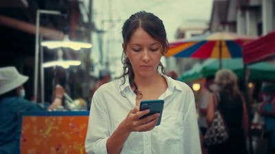 Portrait of a Young Woman Typing on a Smartphone in the Street