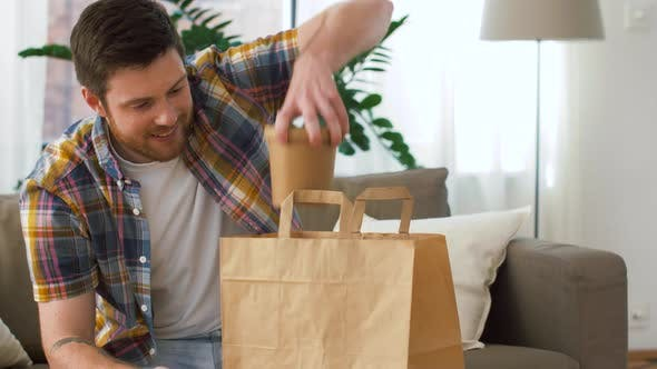 Cover Image for Smiling Man Unpacking Takeaway Food at Home