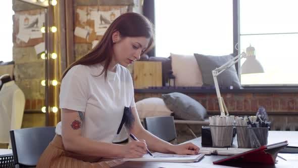 Beautiful Female Designer Drawing Fashion Sketch in Sewing Studio