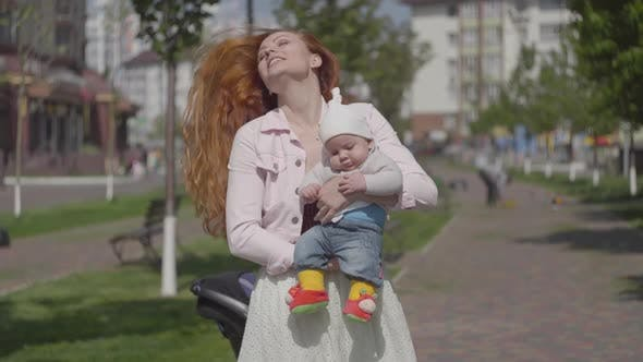 Cover Image for Young Beautiful Redhead Mother Holding a Cute Baby Boy in Her Arms and Talking To Him in a Spring