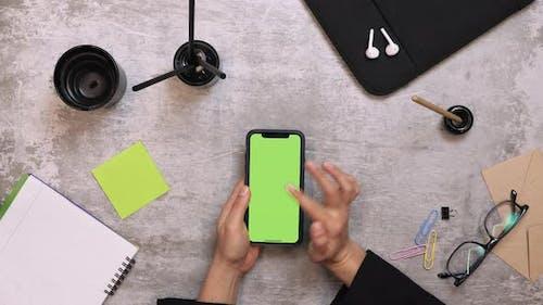 Frau benutzt Smartphone mit Greenscreen, scrollt Nachrichten, tippt auf Fotos, schaut Nachrichten