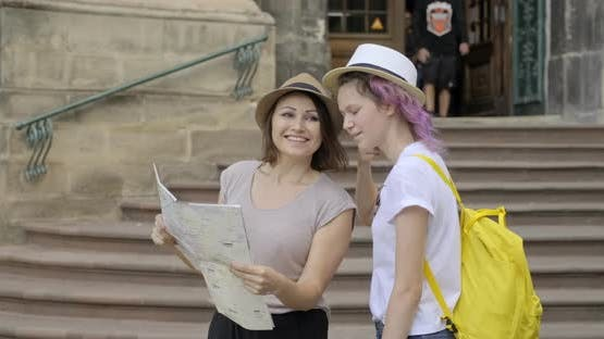 Mother and Teenage Daughter in Old Tourist City with Map