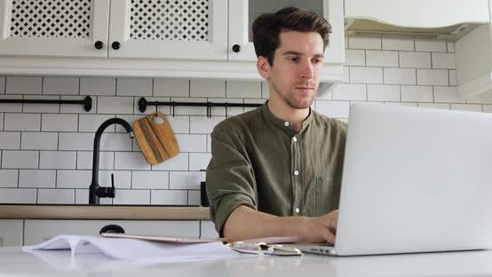 Thumbnail for Man sitting in the kitchen and coding html on laptop. IT sphere. Working from home concept