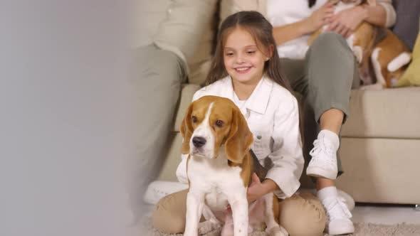 Thumbnail for Happy Little Girl Cuddling Cute Beagle Dog