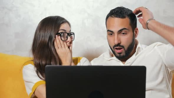 Shocked Couple Before Laptop