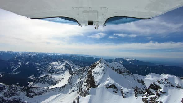Cover Image for Cinematic View Of Helicopter Flying Above Sunkissed Snowy Mountain Peak In Cascade Mountains