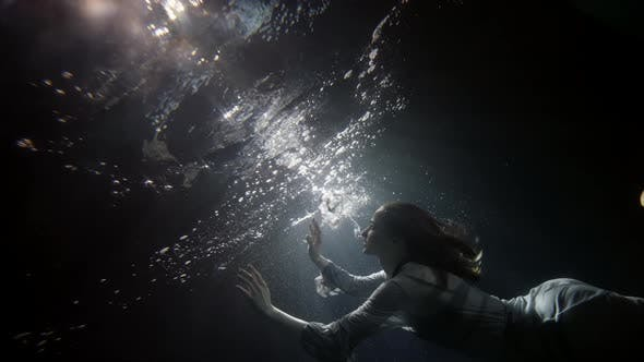 A Beautiful Woman in a Flowing Dress Floats Under the Water on a Dark Background She Swims To the