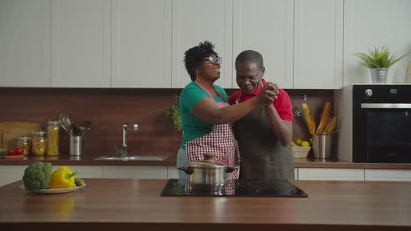 Happy Senior Couple Dancing in Domestic Kitchen