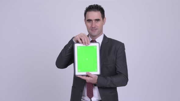 Thumbnail for Happy Handsome Businessman Showing Digital Tablet