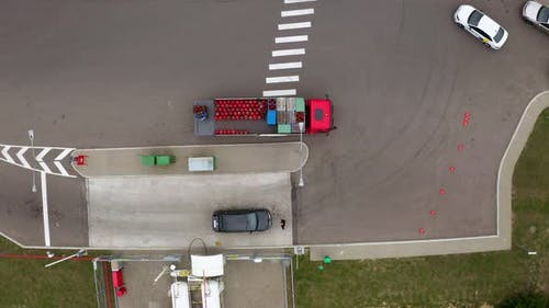A car with red gas cylinders at a gas station. Top view from drone
