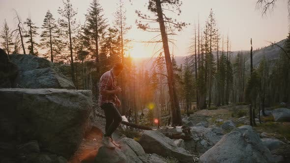 Thumbnail for Successful Young Male Blogger Jumping Off a Big Forest Stone, Hikes on Rocks at Amazing Yosemite