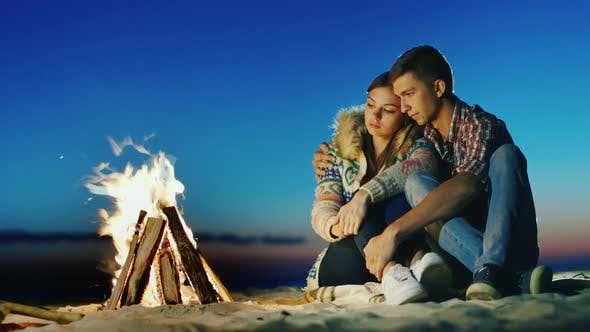 Thumbnail for Romantic Young Couple Sitting on the Beach Campfire. Hug, Admiring the Fire, Dreaming