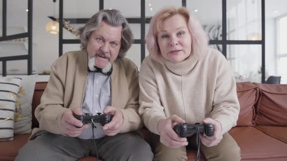 Cover Image for Middle Shot of Funny Senior Couple Playing Video Games. Portrait of Cheerful Caucasian Husband and