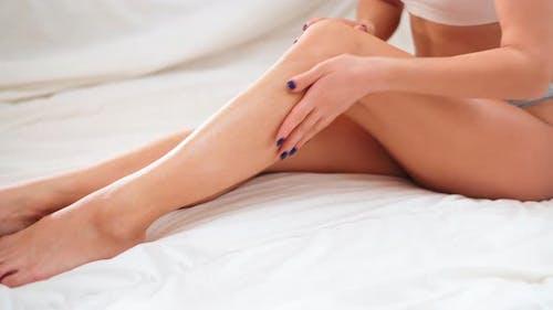 Woman Applying Moisturizer Cream on Her Slim Legs in Bed