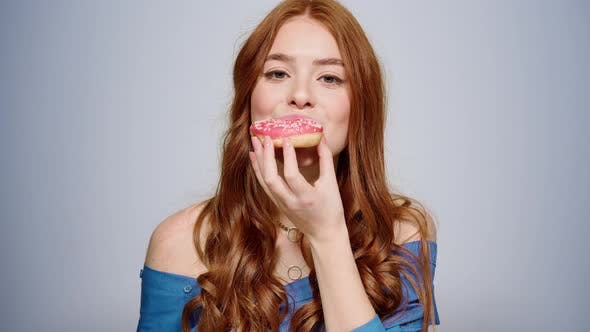 Smiling Woman Eating Doughnut Indoors